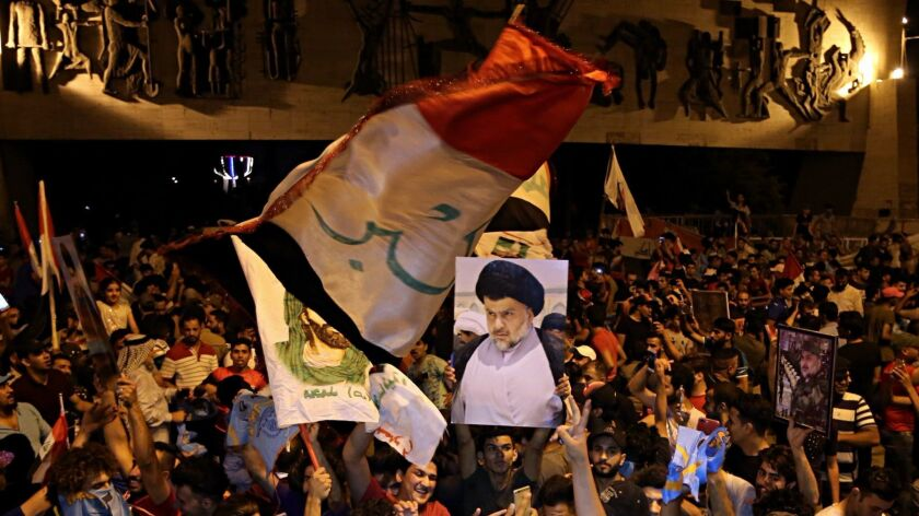 Followers of Shiite cleric Muqtada al-Sadr, seen in the poster, celebrate in Tahrir Square, Baghdad,