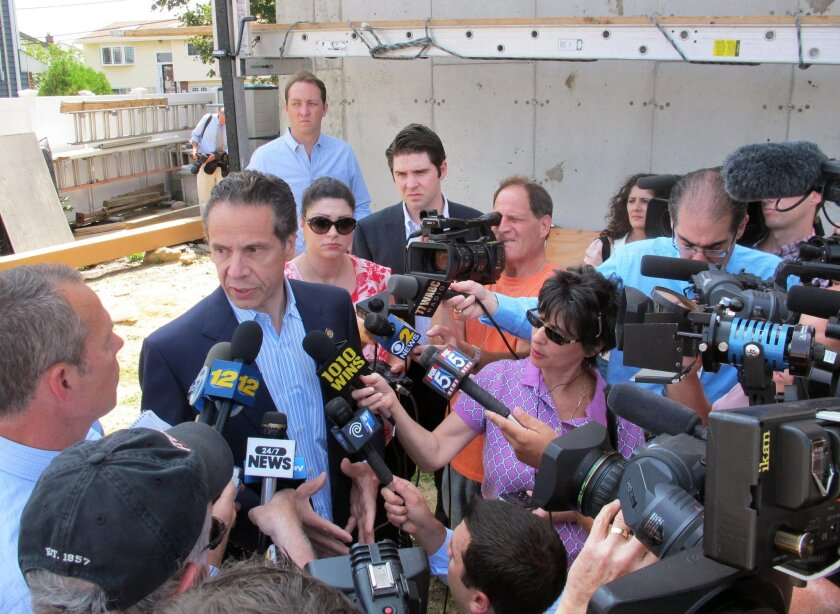 New York Gov. Andrew Cuomo, center left, is surrounded by the media in Freeport, N.Y., where he was visiting a homeowner still rebuilding from Superstorm Sandy, Wednesday, July 30, 2014. Cuomo was on Long Island to announce a new program to help victims of Superstorm Sandy, but ended up fielding questions about the political storm regarding his top aide's efforts to stop the corruption commission from issuing subpoenas to groups linked to the governor. (AP Photo/Frank Eltman)