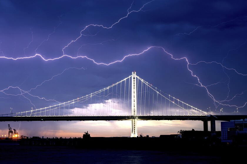 Lightning forks over the San Francisco-Oakland Bay Bridge as a storm passes over Oakland.