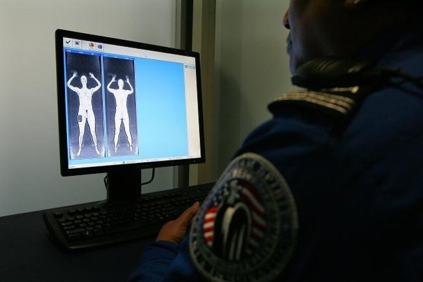 In a frosted-glass screening booth, TSA instructor Dale Paguirigan reviews a demonstration image from the new full-body scanner at Lindbergh Field in San Diego.