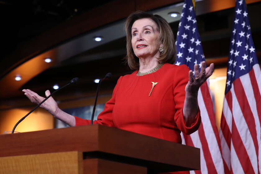 Speaker of the House Nancy Pelosi at a lectern with two U.S. flags behind her