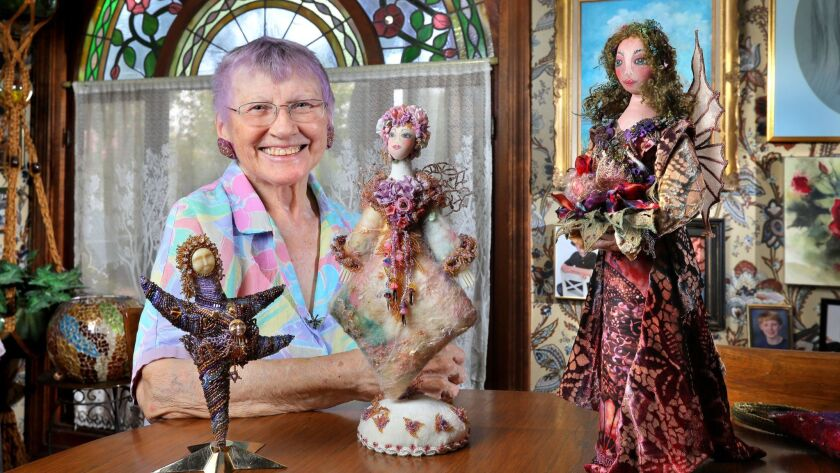 Portrait of artist Rita Zerull in her home in Escondido with three of the art dolls she created.