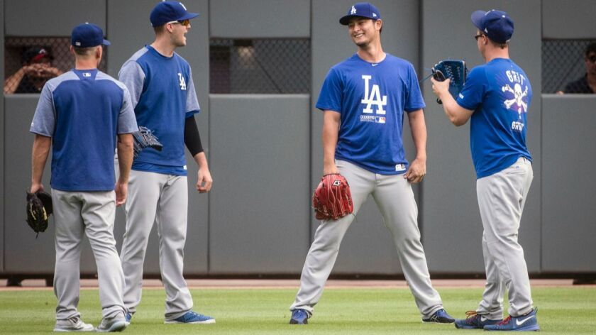 Dodgers' Yu Darvish, second from right, Austin Barnes, left, Alex Wood and Joc Pederson, right, talk