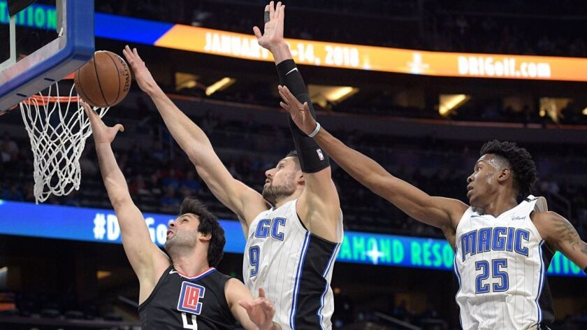 Clippers guard Milos Teodosic (4) has his shot blocked by Orlando Magic center Nikola Vucevic (9) as forward Wesley Iwundu (25) helps defend during the first half on Wednesday.
