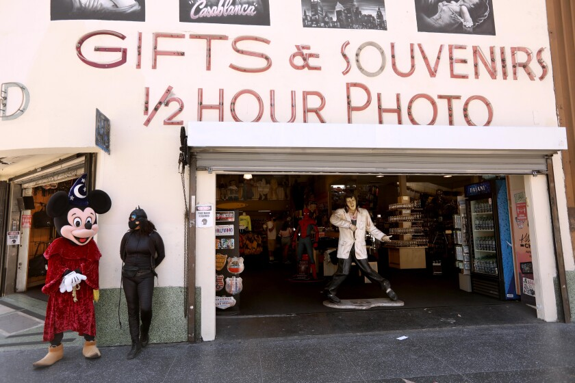 Street performer Javie Rubio, dressed as Mickey Mouse, waits for customers to pose with in front Souvenirs of Hollywood.