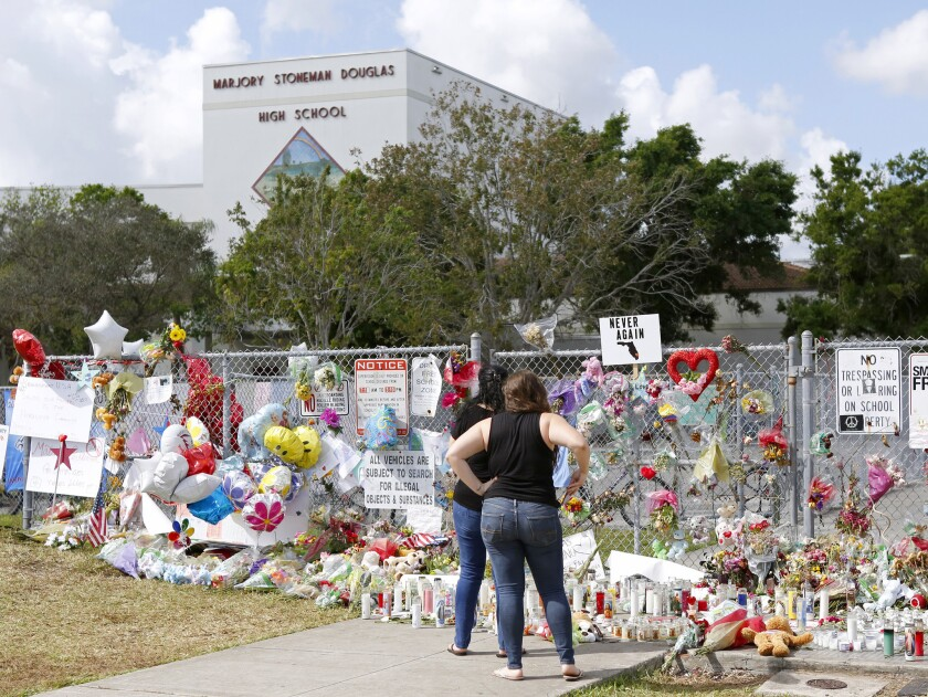Mourners bring flowers as they pay tribute at a memorial for the victims of the shooting at Stoneman Douglas High School on Feb. 25, 2018, during an open house as parents and students returned to the school for the first time since 17 people were killed in a mass shooting at the school in Parkland on Feb. 14, 2018.