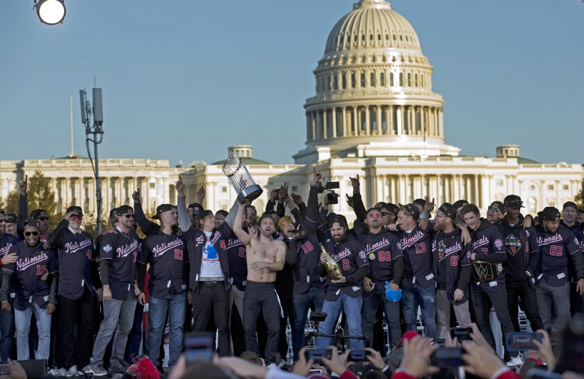 Washington Nationals players raise the World Series trophy during a rally following a  parade on Saturday in Washington D.C.