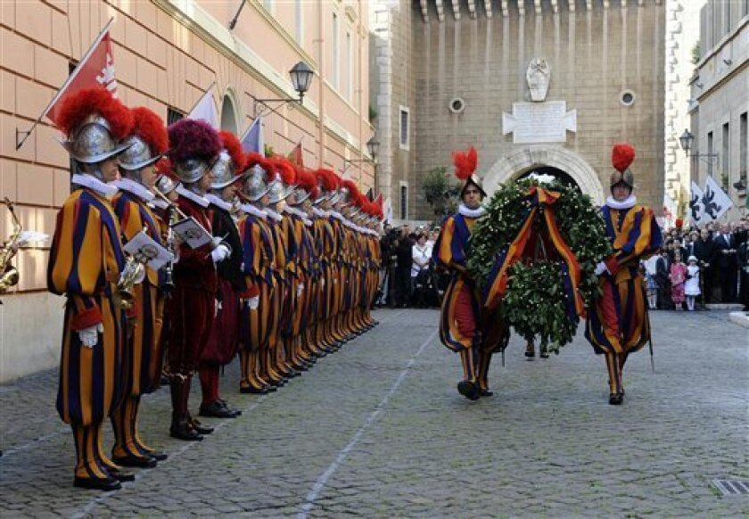 Vatican Swiss Guards carry a commemorative wreath during a celebration of the 1527 Sack of Rome, in the courtyard of the headquarters of the Swiss Guards, at the Vatican, Wednesday, May 6, 2009. On Wednesday afternoon, the Swiss Guards will swear in 32 new recruits. The ceremony is held each May 6 to commemorate the 147 Swiss Guards who died protecting Pope Clement VII during the 1527 Sack of Rome. (AP Photo/Danilo Schiavella, pool)