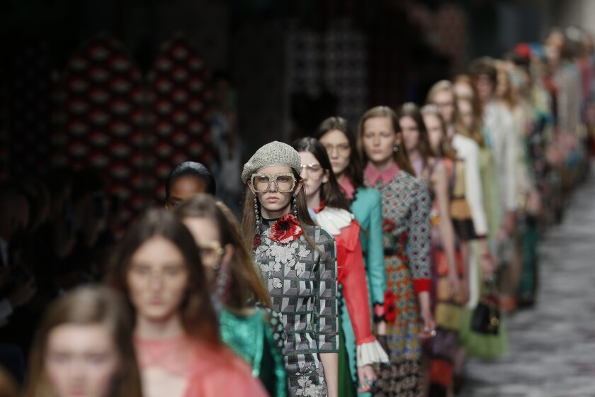FILE - In this Sept. 23, 2015 file photo, models wear creations for Gucci women's Spring-Summer 2016 collection, part of the Milan Fashion Week, unveiled in Milan, Italy. Italian fashion house Gucci is launching $1.5 million in U.S. university scholarships aimed at reaching students who are ''traditionally underrepresented'' in the fashion industry. The scholarship program is part of Gucci's multi-pronged response to the uproar over an $890 sweater that resembled blackface. (AP Photo/Luca Bruno, File)