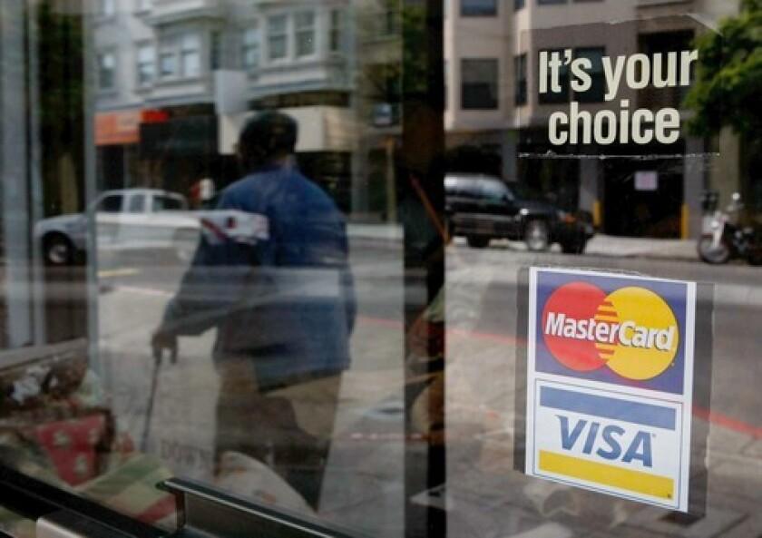 A man walks past a shop window displaying a MasterCard and Visa credit card sign.