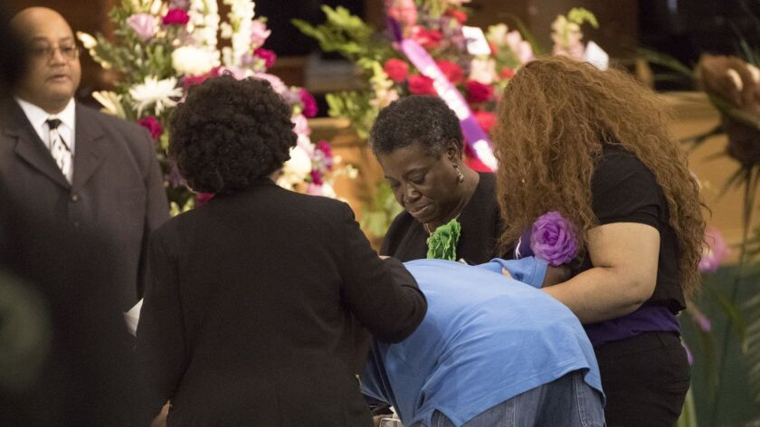 Three women help support a man as he becomes emotional near the casket of Jazmine Barnes during the girl's funeral Tuesday in Houston.