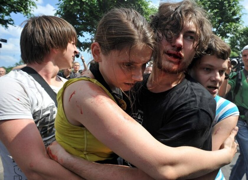 Gay rights activists embrace after clashes with anti-gay demonstrators during a gay pride event in St. Petersburg in June. Russian police arrested dozens of people.