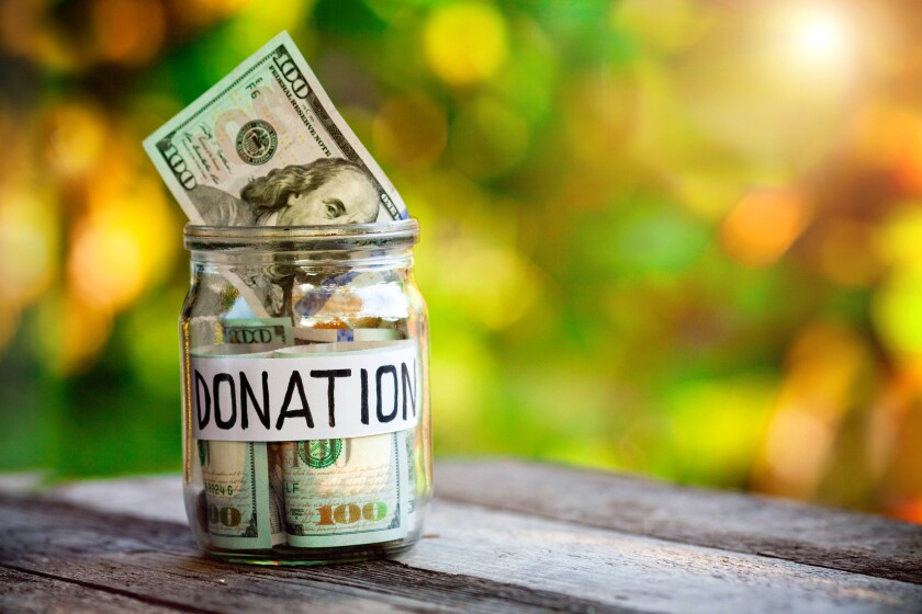 Glass jar with dollars and the word donation paper label. Saving Money , donation concept.