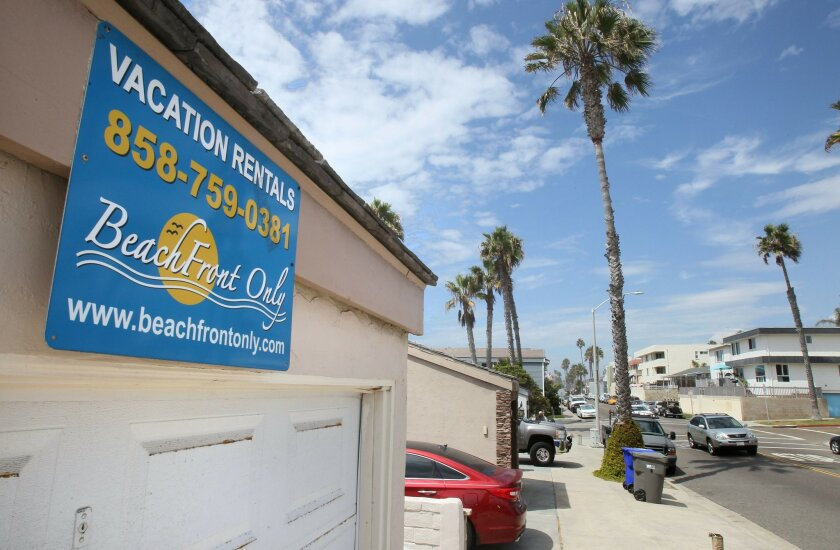 A sign on a garage announces vacation rentals on the 1200 block of South Pacific Street near Oceanside Blvd. It's beach front property.