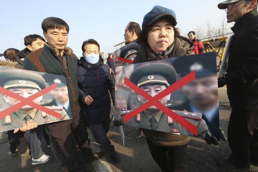 Family members of victims of the sunken South Korean naval ship Cheonan by a North Korean attack hold defaced the portraits of Kim Yong Chol, vice chairman of North Korea's ruling Workers' Party Central Committee, as they march toward the Unification bridge during a rally against his visit in Paju, South Korea, Sunday, Feb. 25, 2018.