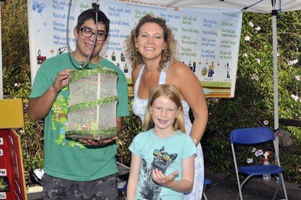 Miguel Preciado holding a ladybug enclosure, Constance Taylor with Sheridan
