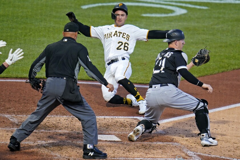 Pittsburgh Pirates' Adam Frazier (26) begins his slide and scores ahead of the throw to Chicago White Sox catcher Zack Collins, right, with umpire Vic Carapazza, left, watching the play during the sixth inning of a baseball game in Pittsburgh, Tuesday, June 22, 2021. Frazier scored on a single by Bryan Reynolds off White Sox starting pitcher Lucas Giolito. (AP Photo/Gene J. Puskar)