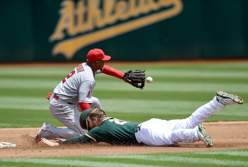 Oakland's Stephen Vogt dives into second base, beating the throw to Angels' Erick Aybar.