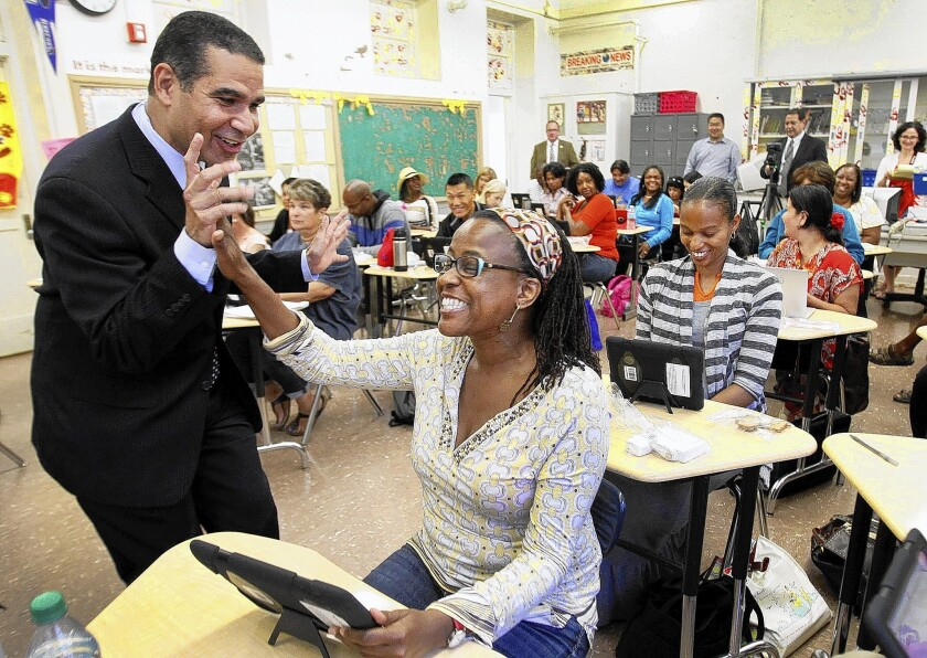 LAUSD Deputy Supt. Jaime Aquino gives a high five to Hillcrest Elementary School teacher Rhonda Marie Smith as teachers attend a iPad training class in 2013. Aquino is no longer with the district.