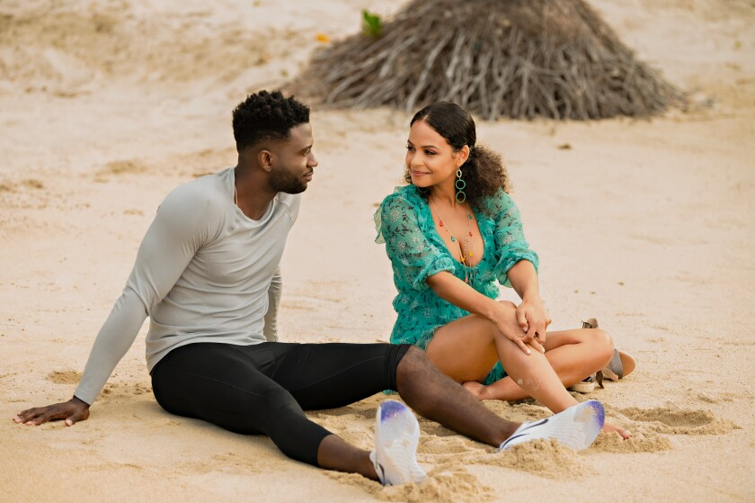 A man and woman sit on a beach