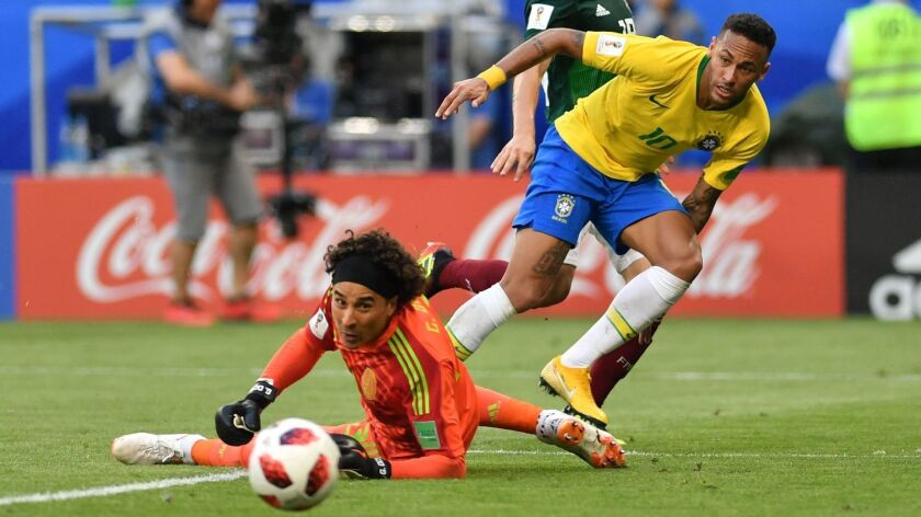 Brazil forward Neymar (10) slips a pass around Mexico goalkeeper Guillermo Ochoa to set up a goal Monday.