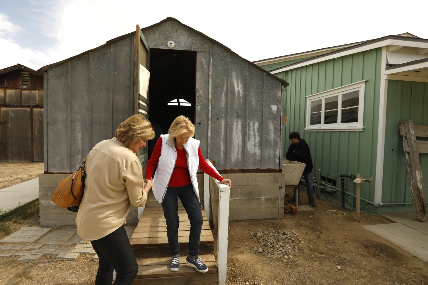 BAKERSFIELD, CA - OCTOBER 19, 2019 - - Pat Rush, 84, with the help of her daughter Angie Trigueiro, , exits one of the structures she and her family used to live in after migrating from Oklahoma to Bakersfield in 1945. Rush was revisiting the Weedpatch Camp with her daughter in Bakersfield on October 19, 2019. After three decades, the Dust Bowl Days festival at Weedpatch Camp, which housed Okies and migrant workers during the Dust Bowl, is ending its run. The final festival celebrates Okie history. (Genaro Molina / Los Angeles Times)