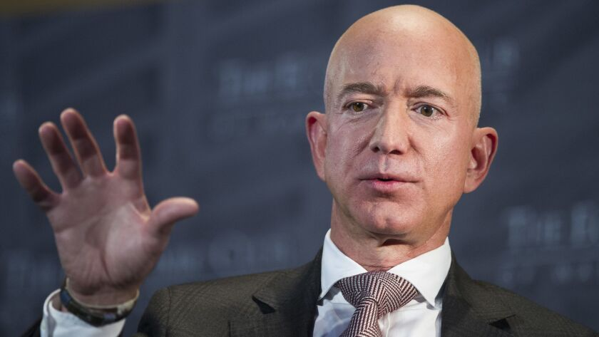 Amazon CEO Jeff Bezos accused the National Enquirer of threatening to publish revealing photos of him unless he backed off an investigation of the magazine.