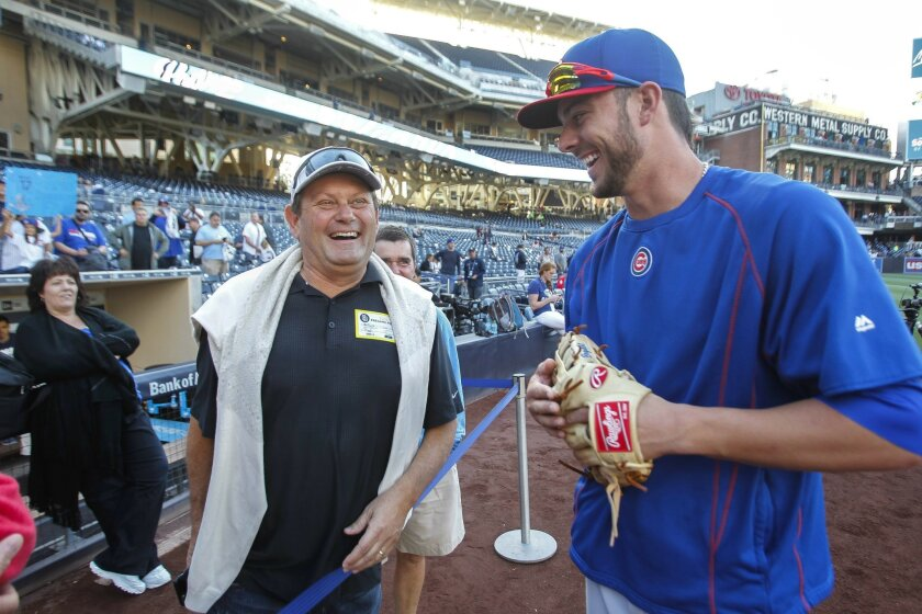 The Cubs' Kris Bryant, right, who played for USD, talks to Mark Cole, who said he helped coach Bryant when he was younger, as Bryant's mother Susie Bryant, left, stands nearby during the Cubs' batting practice before the Cubs game against the Padres at Petco Park in San Diego on Tuesday.
