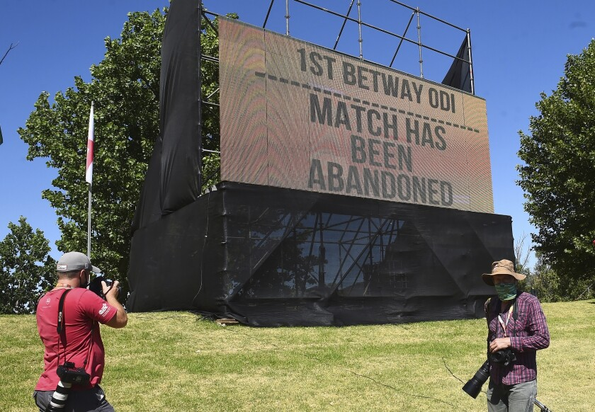 A board announces Sunday, Dec. 6, 2020, that the first ODI cricket match between England and South Africa at Boland Park in Paarl, South Africa has been abandoned due to a COVID-19 scare. The match had been postponed from Friday to Sunday and shifted from Cape Town to Paarl. (AP Photo)
