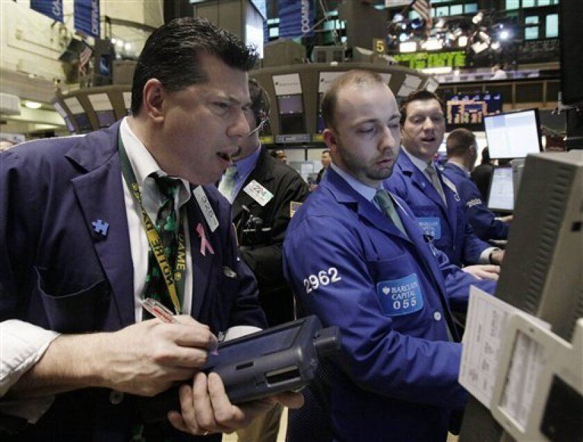 FILE - In this file photo taken March 17, 2011, traders gather at a post on the floor of the New York Stock Exchange. World stocks fell Tuesday, March 29, on more bad news from Japan, where authorities raced to stop a radiation leak from a nuclear power plant damaged in an earthquake nearly three w