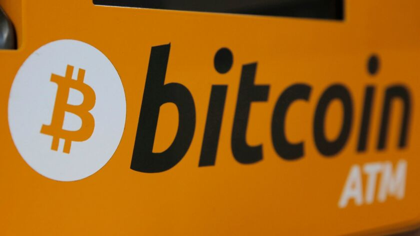 A bitcoin logo is displayed on an ATM in Hong Kong.