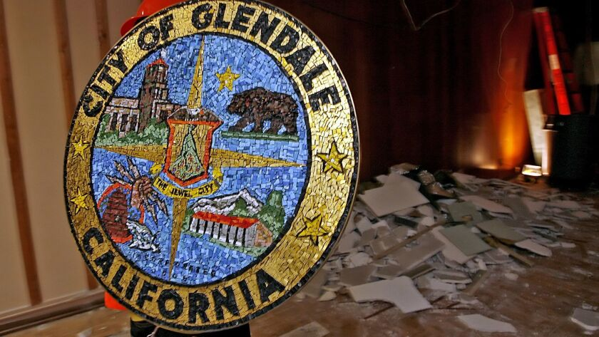 City of Glendale worker removes the city seal from the City Hall Council Chambers on Thursday mornin