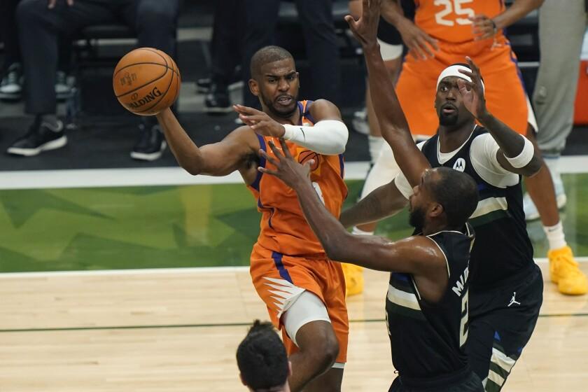 En foto del martes 20 de julio del 2021, el base de los Suns de Phoenix Chris Paul intenta pasar el balón al alero de los Bucks de Milwaukee Khris Middleton en el juego 6 de las Finales. El miércoles 21 de julio del 2021, los Suns esperan mantener a su equipo para la próxima temporada. (AP Photo/Paul Sancya)