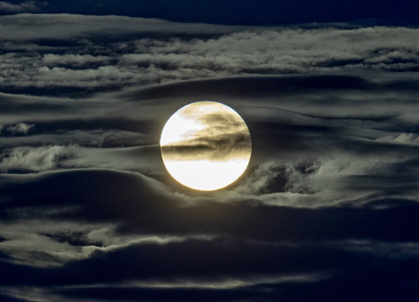 A full moon surrounded by clouds