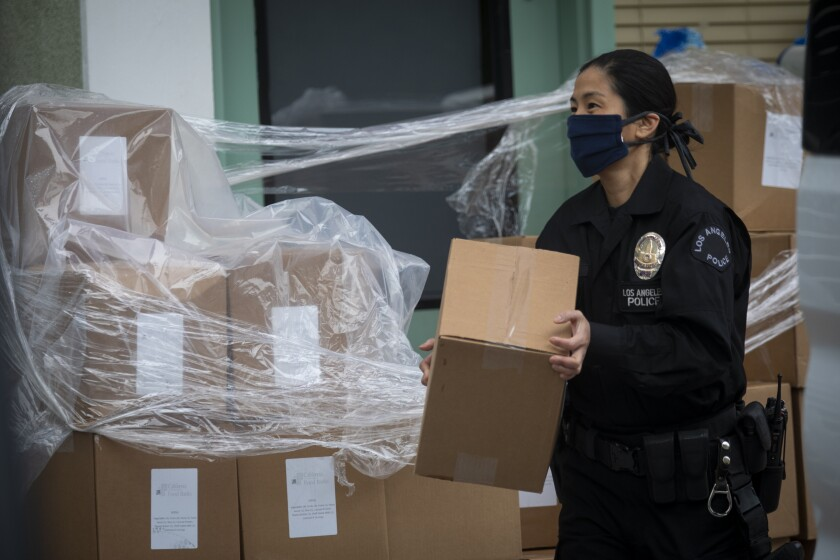 LAPD Officer Kat Piamonte carries a box of supplies during food distribution effort in Hollywood on Thursday.