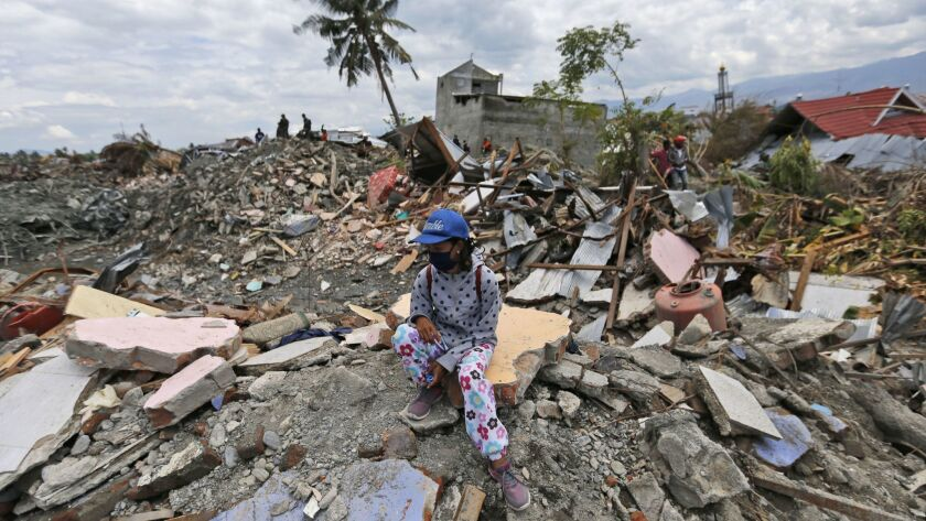 A woman sits on a pile of rubble in an area devastated by an earthquake in the Balaroa neighborhood of Palu, Indonesia, on Oct. 8.