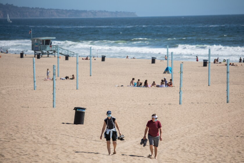People walk along the sand in Manhattan Beach on Friday.