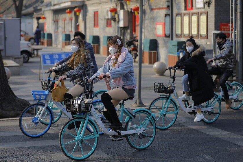 People wear masks riding bicycles outside Jingshan Park in Beijing last month.