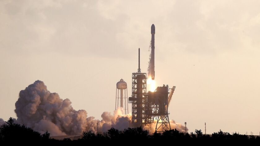 A Falcon 9 SpaceX rocket carrying a classified satellite for the National Reconnaissance Office lifts off at Kennedy Space Center in Florida.