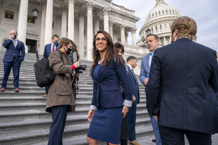 FILE - In this Jan. 4, 2021, file photo, Rep. Lauren Boebert, R-Colo., center, joins other freshman Republican House members for a group photo at the Capitol in Washington. The district's newest representative, Boebert, is an unabashed, social media-savvy loyalist of former President Donald Trump who, like her fellow first-term colleague GOP Rep. Marjorie Taylor Greene of Georgia, is stoking controversy with her far-right views and defiant actions. But unlike Greene, Boebert doesn't hail from an overwhelmingly GOP, safe district. (AP Photo/J. Scott Applewhite, File)