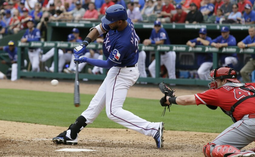 Texas Rangers Nomar Mazara (30) hits an RBI single in front of Los Angeles Angels catcher Jett Bandy (47) during the sixth inning of a baseball game in Arlington, Texas, Wednesday, May 25, 2016. Rangers' Rougned Odor scored on the play. (AP Photo/LM Otero)