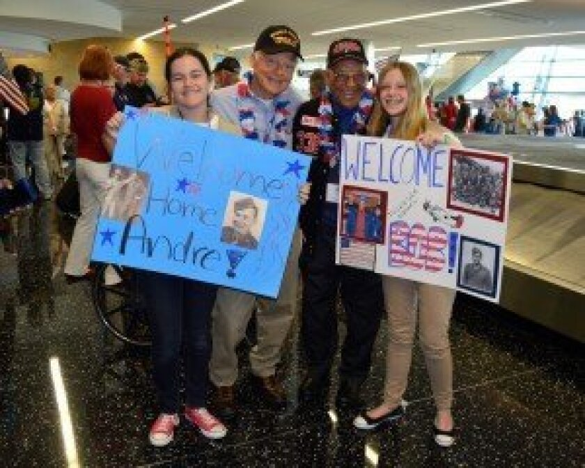 """For their cookie-funded Silver Award project, Girl Scouts Eve Maldonado (left) and Roni Nelson (right) of Rancho Santa Fe are supporting Honor Flight San Diego, a local nonprofit. They recently welcomed World War II veterans Andre Chappaz and Tuskegee Airman Lt. Col Bob Friend at the San Diego International Airport as part of Honor Flight's """"Hero's Welcome Homecoming."""" The girls are also among the many Girl Scouts participating in the annual Memorial Day flag placement ceremony at Rosecrans National Cemetery."""