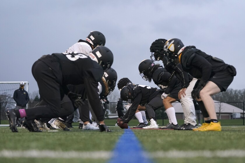 College football players wait for the snap on the line of scrimmage during practice.