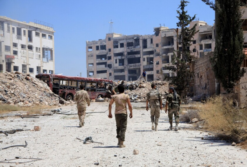 Syrian army soldiers patrol the area around the entrance of Bani Zeid after taking control of the previously rebel-held district of Leramun, on the northwest outskirts of Aleppo, on July 28, 2016.
