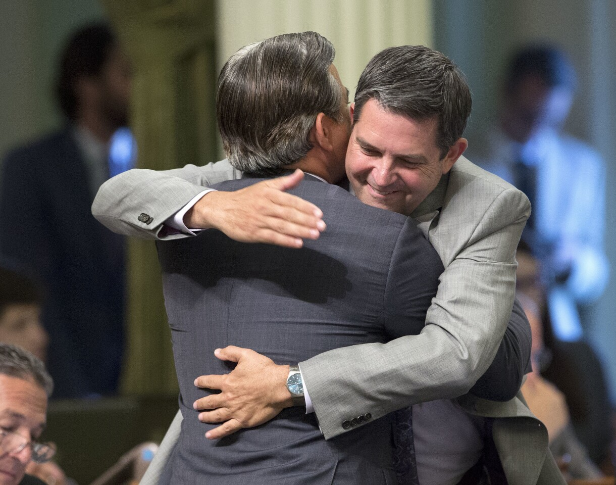 Assemblyman Rob Bonta (D-Alameda), left, receives congratulations from Assemblyman Jim Wood (D-Healdsburg) after the Assembly approved his measure to end surprise medical bills from out-of-network doctors, on the final day of the legislative session in Sacramento.