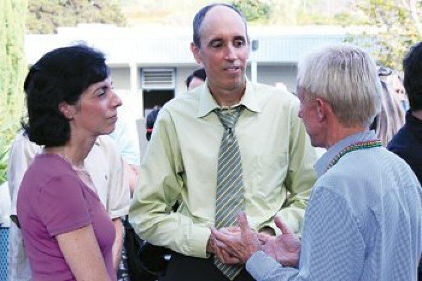 Sixth-grade parents Lisa Galstian and John Gartner chat with sixth grade world history teacher Mark Heinze.