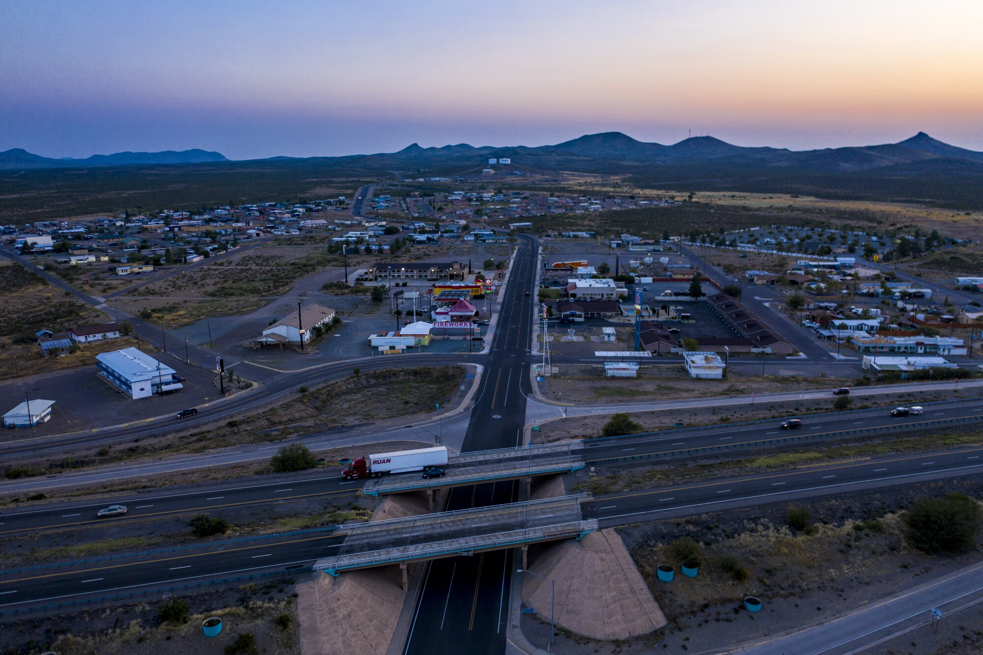 A truck rolls past the Main St. exit on Interstate 10, dividing the rural town of Lordsburg, NM.