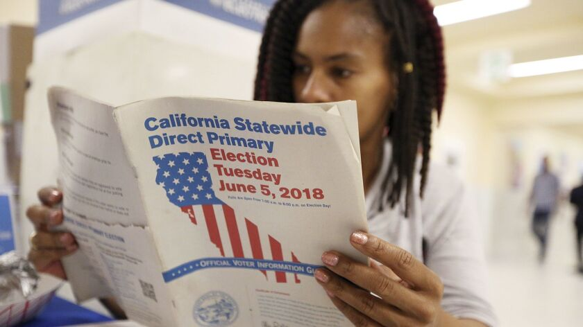 Nikko Johnson reviews the California Primary election guide at San Francisco City Hall Tuesday, June