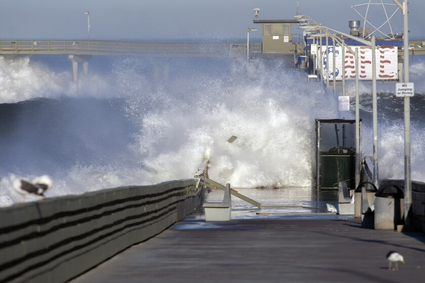 Waves crash over the Ocean Beach pier on Monday, January 11, 2021, damaging the pier.