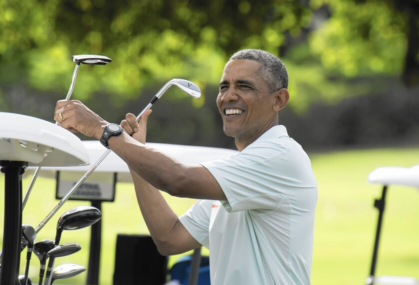 President Obama, pictured Wednesday on his Christmas vacation, has considerably more white in his hair than when he took office.